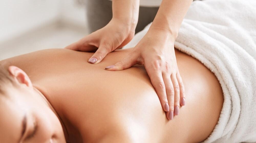 Lichaamsverzorging. Jong meisje met massage, ontspannen in spa salon, close-up.