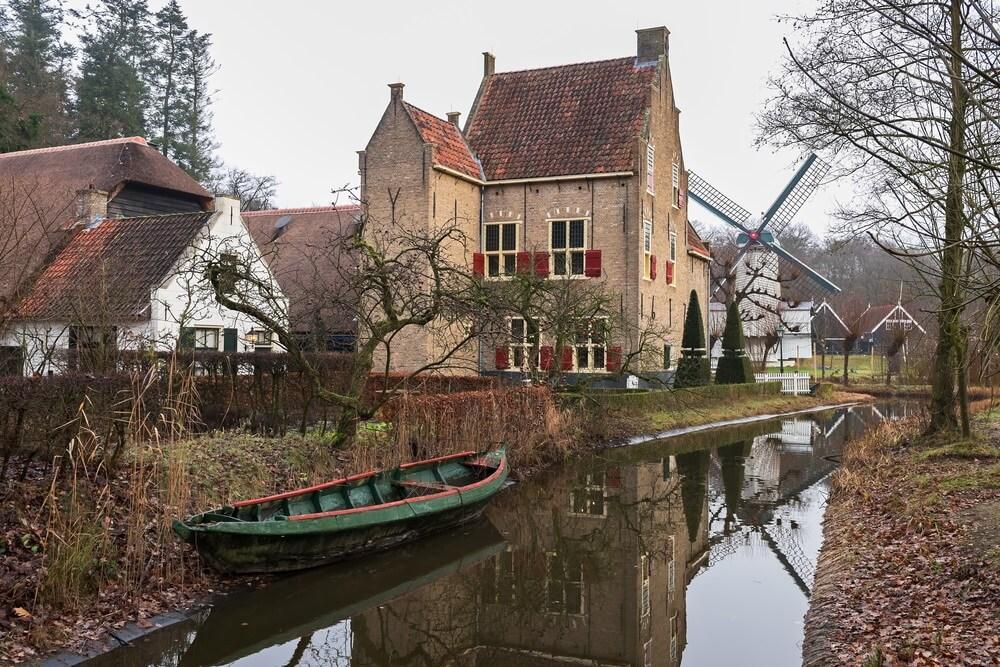 Historische kasteelboerderij aan de oevers van de gracht in het openluchtmuseum van Arnhem, Nederland.