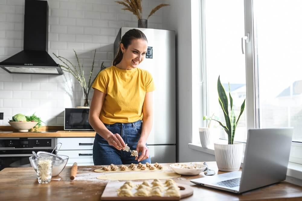 Een jonge vrouw leert koken, ze bekijkt videorecepten op een laptop in de keuken en kookt een gerecht van het deeg. Online cursus gratis.