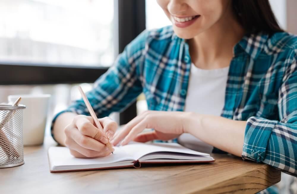 Elegante slimme vrouw die haar ideeën opschrijft tijdens een gratis cursus reisjournalistiek.