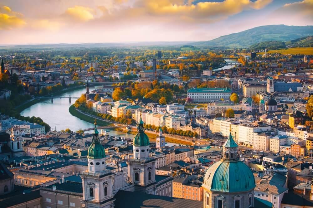 Prachtig luchtfoto panoramisch uitzicht in een herfst seizoen in een historische stad Salzburg met Salzach rivier in mooie gouden avondlicht hemel en kleurrijk van de herfst bij zonsondergang, Salzburger Land, Oostenrijk.