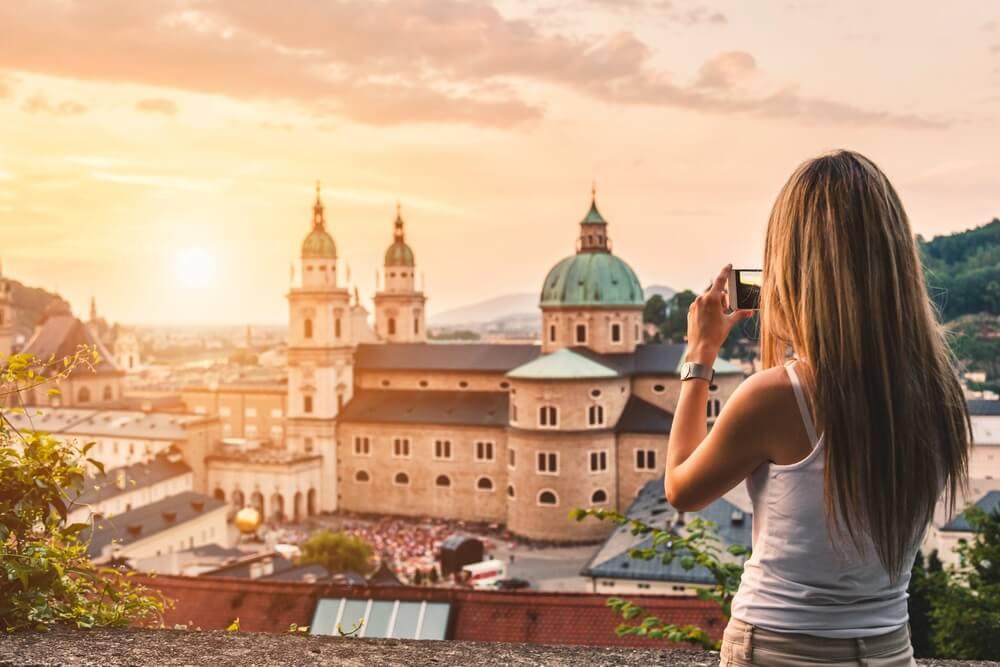 Toerist het nemen van een foto met mobiel van prachtige zonsondergang in Salzburg Oostenrijk.
