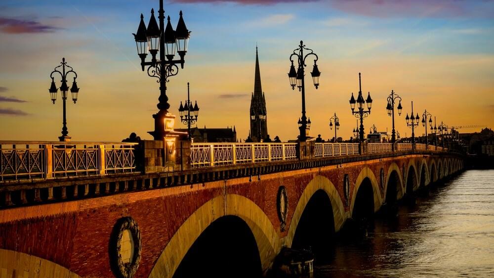 Pont de Pierre-brug en bewegingsonscherpte van tram in Bordeaux bij zonsondergang als de scène van de nachthemel.