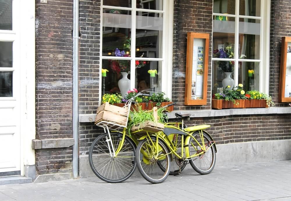 Twee fietsen staan tegen een oude gevel van een historische gebouw aan in Den Bosch, Nederland.