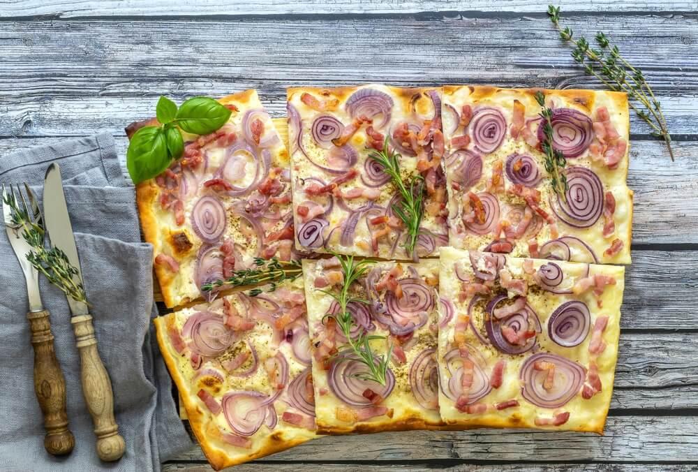 Traditionele gesneden Duitse pizza of flammkuchen - open taart met spek, rode ui en verse room.