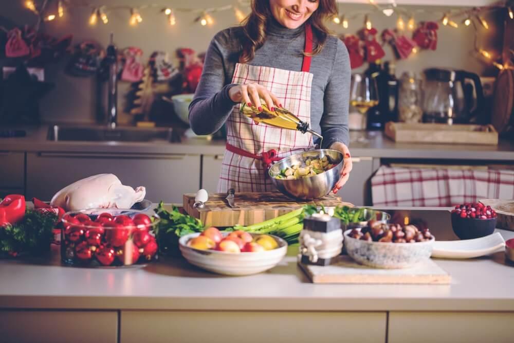 Jonge Vrouw Koken in de keuken. Gezonde voeding voor Kerstmis (gevulde eend of gans).