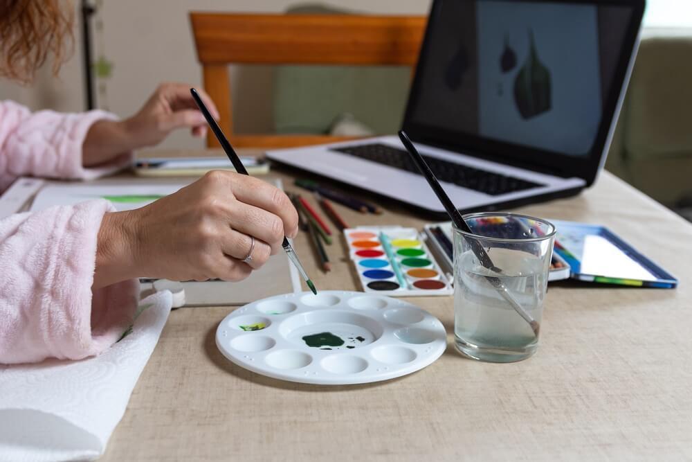 Vrouw volgt een online cursus aquarel schilderen.
