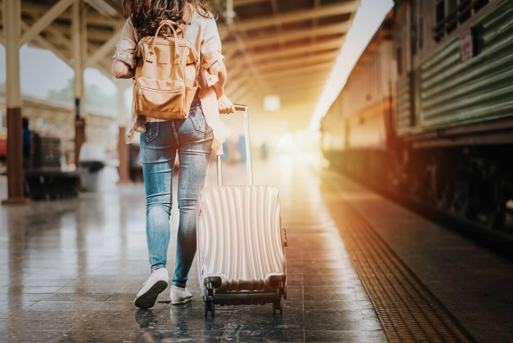 Vrouwelijke reiziger  met bagage op het treinstation. Treinvakanties.